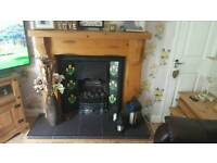 Cast iron gas fire with tiled surround. Faux coles and grill included.