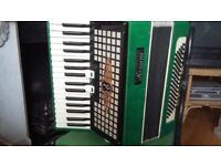 Lovely green piano accordian in decent working order made by Rossini.
