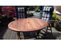 Solid hardwood circular table and four chairs with cushions.