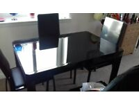 BLACK GLASS DINNING TABLE WITH 4 CHAIRS FAUX LEATHER WITH METAL LEGS ON THE TABLE AND CHAIRS