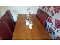 Very heavy solid oak table and 6 red leather chairs