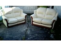 A pair of cream leather two seater sofas