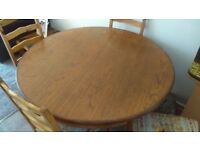 Circular (extending to oval) dining table and 4 chairs.