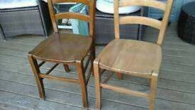 Two wooden dining table chairs