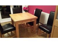 Oak dining table with 4 black leather chairs