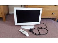 A small white samsung flat screen tv with remote control