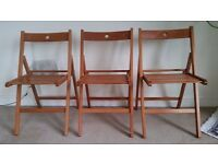 Three folding wooden chairs