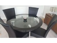 Glass round dining table with 4 black faux leather chairs with chrome legs. Immaculate condition