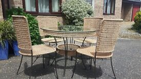 Glass toped wicker and and cast iron table and 4 chairs