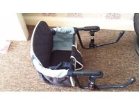 Travel highchair attaches to table for feeding. Collapses flat for travel.