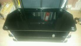 Black glass tv unit could hols up to a 55 inch tv