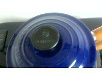 Le Creuset cast iron pans. Blue with wooden handles.