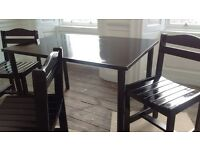 Black table & three chairs plus metal coat stand. Table is 120cm by 80cms.