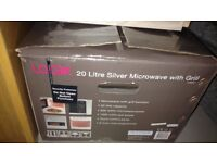 Used, functioning, medium size digital, silver Logik microwave with grill