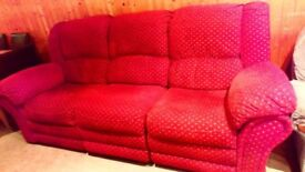 Orangy-red three seater comfy settee- two ends are recliners.