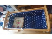 A wooden pine baby rocking crib with mattress, bed sheet and bumpers.
