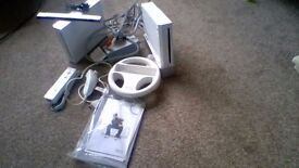 2 Nintendo wii consoles with remote and wii steering wheel