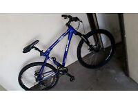 A dark blue gt aggressor mountain bike with silver stripe white writing black handel bars