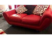 Two seater red leather sofa with footstool