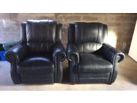 Two single black leather armchairs.
