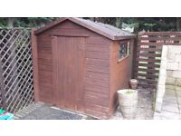 Garden Shed 6 feet by 8 feet; wooden with windows each side.