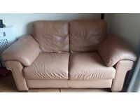Used two-seater tan leather sofa