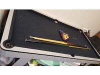 Pool table with cues, balls and chalk