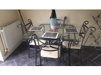 Kitchen table and chairs. Glass table top, non adjustable legs, 4 chairs slight marks on seats