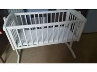 White swinging crib and mattress