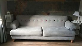 Modern grey DFS sofa with coloured design.