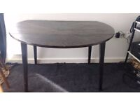 Circular wooden drop-leaf dining table