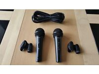 two brand new behringer microphones with mic clips and a lead