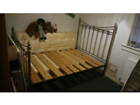 3/4 size metal bedframe with wooden slats.