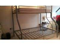 A triple bunk bed comprising of a single bed over a double bed with single mattress included.