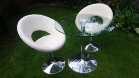 Circular / Round glass dining coffee table - clear glass and two white swivel chairs chrome