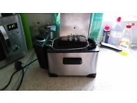 Compact electric deep fat fryer, stainless steel with basket, lid and temperature dial.