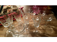 A DOZEN DRINKING GLASSES MOST WITH STEMS AND A GLASS JUG