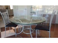 Glass topped circular dining table with six upholstered chairs.
