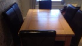 Oak extendable dining table and six brown leather chairs