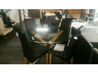A brand new very good quality round glass topped dining table x 4 chairs.