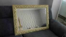 Ornate gold framed, rectangular bevelled edge mirror.