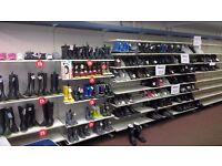 Metal shelving primarily for displaying footwear and boots.