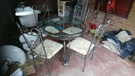 Wrought iron glass top table and four chairs