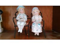 Pair of Vintage glazed porcelain statues of children sitting on wicker chairs drinking