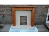 Cream marble fire hearth and back plate with pine surround