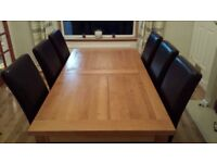 Solid oak extending dining table and six leather chairs with matching large solid oak sideboard
