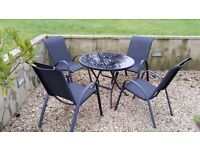 Outdoor glass top table and 4 x black chairs