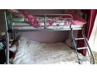 Grey metal triple bunk bed.