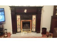 hardwood fire surround with cast iron insert and tiles down sides