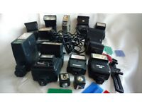 JOB LOT 11 CAMERA FLASHES, SYNC CABLES, AND OPTIC SLAVES.